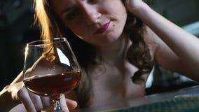 De gedeprimeerde damezitting alleen in bar, die glas brandewijn bekijken, verdeelt stock video