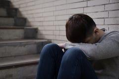 De gedeprimeerde mens zit ondergronds in Royalty-vrije Stock Foto