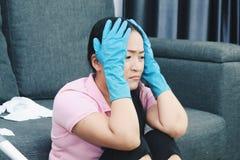 De gedeprimeerde schreeuwende vrouw kijkt stressfully, houdt beide handen op hoofd, draagt beschermende handschoenen, voelt moehe royalty-vrije stock foto's
