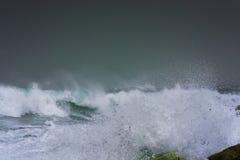 De gedetailleerde golf die van het de winteronweer en op kust breken bespatten Stock Foto
