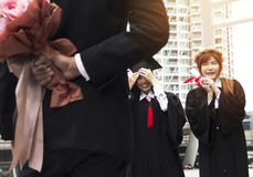 De gediplomeerde behaalt vrouwenglimlach een diploma en is gelukkig na graduatie stock foto's