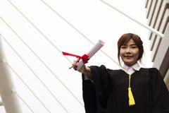 De gediplomeerde behaalt vrouwenglimlach een diploma en is gelukkig na graduatie royalty-vrije stock foto
