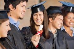 De gediplomeerde Status van Studentenholding diploma while royalty-vrije stock foto