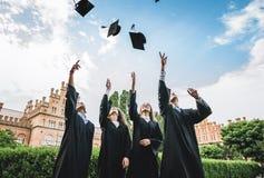 De gediplomeerden dichtbij universiteit werpen op hoeden in de lucht stock foto