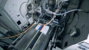 De gedrukte tijdschriften bewegen zich langs de industriële transportband stock video