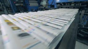 De gedrukte tijdschriften bewegen zich langs de vervoerder Drukkranten in typografie stock footage