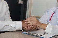 De geduldige hand van de artsenholding & het troosten van hem voor slecht nieuws physi stock afbeeldingen