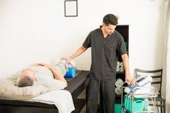 De Geduldige ` s Knie van therapeutpositioning electrodes on in het Ziekenhuis stock afbeelding