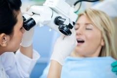 De geduldige ` s tanden van het tandartsonderzoek met microscoop royalty-vrije stock afbeeldingen
