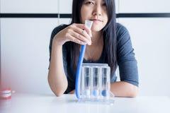 De geduldige vrouw incentivespirometer met behulp van of drie ballen die voor bevorderen long Stock Afbeelding
