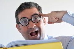De Geekymens denkt over een idee dat hij in een boek heeft gelezen Stock Afbeelding