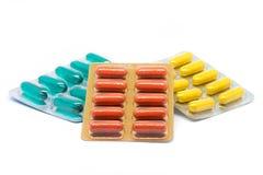 De geelgroene en oranje pillen van gelatinecapsules in blaarpak Stock Foto
