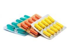 De geelgroene en oranje pillen van gelatinecapsules in blaarpak Stock Fotografie