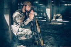 De geestelijke mens zit in het hurkende positie en bidden Hij houdt zijn ogen gesloten en het houden overhandigt samen dicht stock afbeeldingen