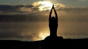 De geestelijke yogi zit in lotusbloem op een meerbank en bidt bij zonsondergang in langzame motie stock video