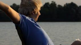 De geeuwende Mens doet een Ontspannende Oefening als Vouwende Voorzitter bij Zonsondergang in slo-Mo stock videobeelden