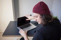 De gefrustreerde gebruiker sluit laptop Een jonge programmeur in de werkplaats heeft problemen op het werk stock foto