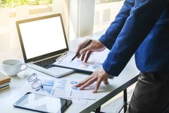 De gegevensdocumenten van de bedrijfsmensen werkende analyse van effectenbeursbedrijf op het kantoor met lege het schermlaptop stock fotografie