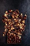 De gehakte achtergrond van de Nootchocoladereep op zwarte/Donkere verpletterde CH Stock Afbeelding