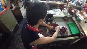 De gehakte vissen van de vissenverkoper verpakking in een slordige natte markt stock footage