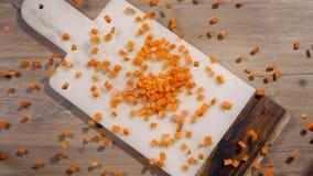 De gehakte wortel valt in langzame motie aan de rotsraad op de lijst, dalende groenten, voedsel in super langzame motie, lijst stock videobeelden