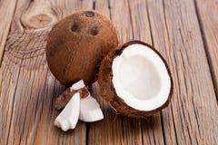De gehalveerde kokosnoot op oude houten achtergrond stock fotografie