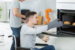 De gehandicapte jonge mens in rolstoel opent oven om voedsel voor te bereiden stock foto