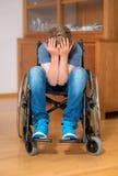 De gehandicapte jongen in rolstoel is droevig Stock Afbeelding