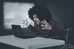 De gehandicapte mens kijkt boos in bureau stock afbeelding