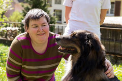 De gehandicapte vrouw is liefkozing een hond Royalty-vrije Stock Foto's