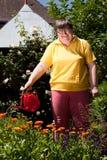 De gehandicapte vrouw met een pot giet bloemen Royalty-vrije Stock Afbeeldingen