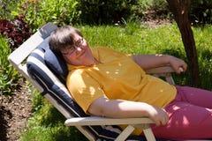 De gehandicapte vrouw zonnebaadt in een ligstoel Stock Foto