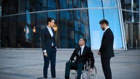 De gehandicapte zakenman in rolstoel en twee zijn collega's heeft positief gesprek stock video