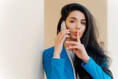 De geheimzinnige donkerbruine vrouw met make-up, besprekingen met commerciële partij, vertelt geheim, maakt stil gebaar, bekijkt  stock fotografie