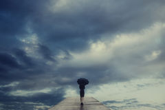 De geheimzinnige vrouw met paraplu kruist een brug aan de surreal mening van de hemel royalty-vrije stock fotografie