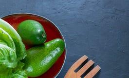 De gehele avocado ligt op een met de hand gemaakte plaat Het concept gezonde het eten vruchten en groenten Mening van hierboven R royalty-vrije stock foto