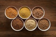 De gehele basis van het voedseldieet - diverse zaden in kommen op bruine lijst royalty-vrije stock afbeelding