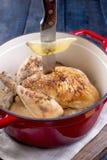 De gehele die kip met citroen en rozemarijn in een rood gietijzer wordt gebakken Blauwe houten achtergrond en grijze handdoek Het stock foto's