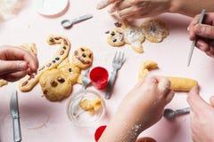 De gehele familie bereidt Kerstmisbroodjes voor Kerstmiskoekjes en peperkoek in de vorm van sneeuwmannen Het voorbereidingen tref royalty-vrije stock foto's