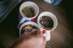 De gehuwde mens met een ring op haar vinger, brouwt uw ochtendkoffie bij ontbijt voor haar familie Stock Afbeeldingen