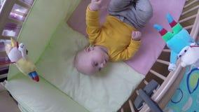 De geinteresseerde baby bekijkt carrouselstuk speelgoed rotatie over bed 4K stock footage