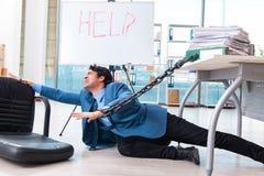 De geketende mannelijke werknemer ongelukkig met het bovenmatige werk royalty-vrije stock afbeeldingen