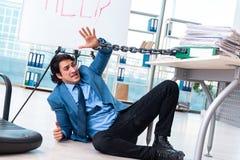 De geketende mannelijke werknemer ongelukkig met het bovenmatige werk stock foto's