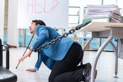 De geketende mannelijke werknemer ongelukkig met het bovenmatige werk stock afbeelding