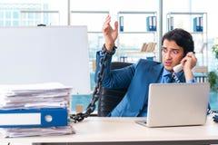 De geketende mannelijke werknemer ongelukkig met het bovenmatige werk stock afbeeldingen