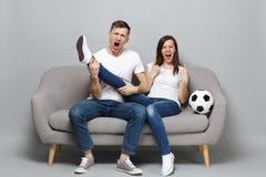 De gekke het gillen de man van de paarvrouw voetbalfans juichen steun omhoog favoriet team met de greepbeen van de voetbalbal zoa stock fotografie
