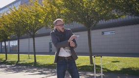 De gekke jonge en gelukkige zakenman danst in jasje het vieren voltooiing outdoors Concept beambte, rust stock footage