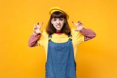 De gekke meisjestiener in Franse baret, denim die sundress als dier grommen, die kat maken krabt gebaar dat op geel wordt geïsole stock foto
