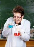 De gekke professor giet blauwe vloeistof Stock Afbeeldingen