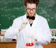De gekke professor overhandigt de fles van Erlenmeyer Stock Fotografie